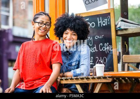 Portrait of boy sitting on mothers lap at sidewalk cafe - Stock Photo