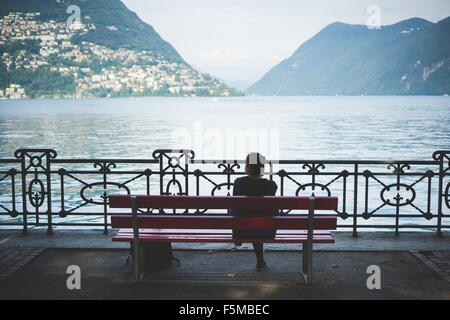 Rear view of silhouetted woman on park bench looking out at Lake Lugano, Switzerland - Stock Photo