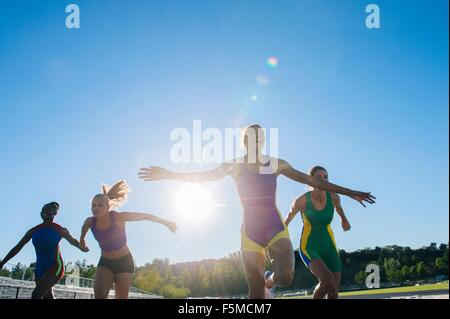 Four female athletes on athletics track, coming to end of race - Stock Photo
