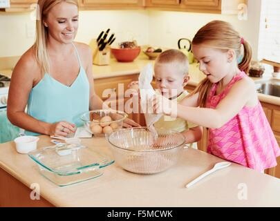 Family preparing batter in mixing bowl - Stock Photo