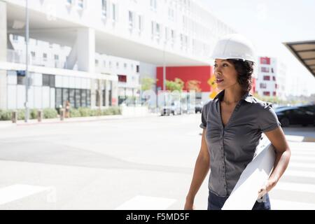 Young woman, wearing hard hat, carrying plans - Stock Photo