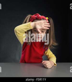 Little girl rubs her forehead over grey background - Stock Photo