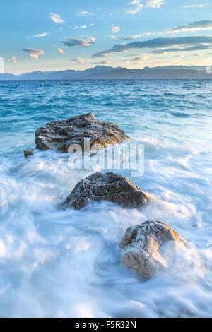 The rocks on Kanoni beach, Kassiopi, Corfu are lit up with the stong orange light of sunrise. - Stock Photo