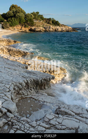 The pebbles and rocks on Bataria and Kanoni beach, Kassiopi, Corfu are lit up with the stong orange light of sunrise. - Stock Photo