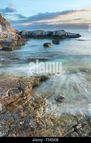 The waves are flowing over the shore at Bataria and Kanoni Beach, Kassiopi, Corfu, Greece. - Stock Photo