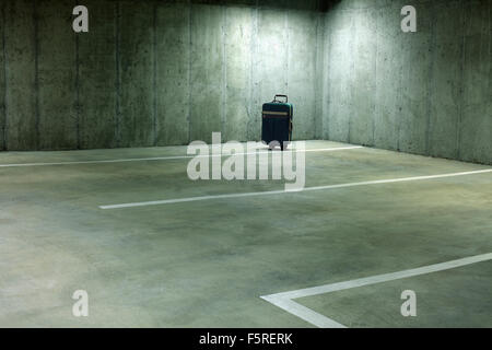 Forgotten Suitcase in Empty Parking Garage - Stock Photo
