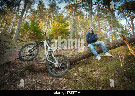 Sweden, Vastergotland, Lerum, Mountain biker sitting on tree trunk - Stock Photo