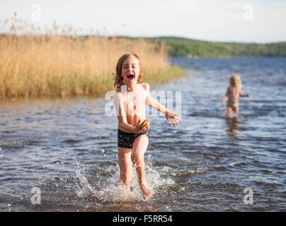 Sweden, Vastergotland, Lerum, Lake Aspen, Boy (8-9) and girl (6-7) playing in lake - Stock Photo