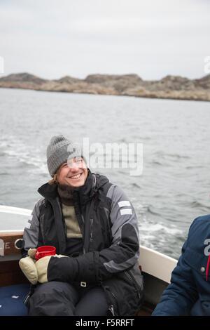 Sweden, Bohuslan, Marstrand, Portrait of mature man on motor boat - Stock Photo