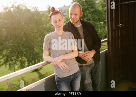 Sweden, Vasterbotten, Norrmjole, Young couple standing on balcony - Stock Photo