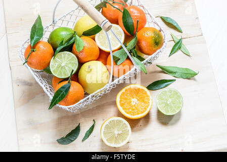 Assorted citrus fruit , leaves on, in a white wire basket, some halved, on a wooden tray background, seen from above - Stock Photo