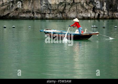 Woman in wooden rowboat and pearl farm buoys, Vung Vieng fishing village, Ha Long Bay, Bai Tu Long Sector, near - Stock Photo