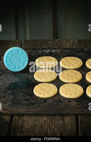 Uncooked shortbread before being to be baked, with blue stamp with inscription Home Made. Over black cutting board. - Stock Photo
