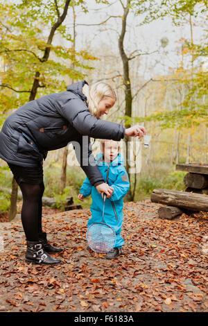 Mother assisting son in playing badminton - Stock Photo