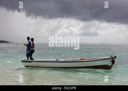 Two African boys are fishing on a boat. - Stock Photo