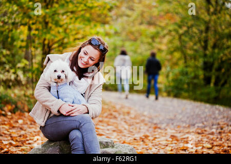 Happy woman looking at Bichon Frise while sitting on rock - Stock Photo