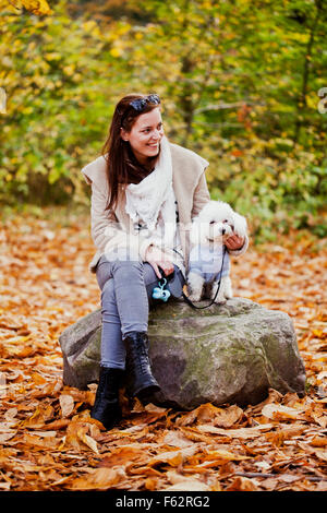 Happy woman with Bichon Frise sitting on rock in forest - Stock Photo