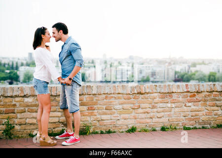 Young and beautiful couple in love being close to each other outdoors and about to kiss - Stock Photo