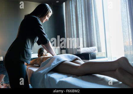 Young and beautiful massage therapist massaging client with beautiful legs lit by the window light - Stock Photo