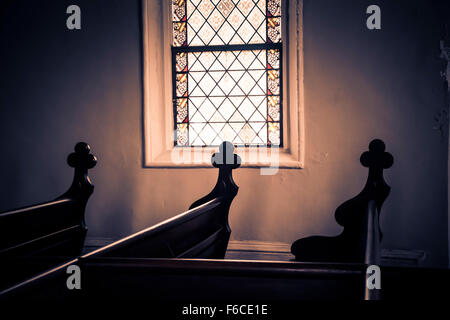 A dimly lit interior from a stained glass church window with carved crosses decoratively set on the ends of each - Stock Photo