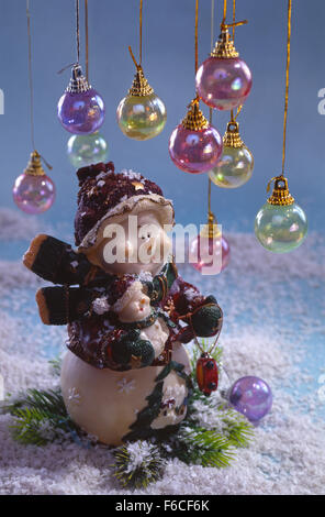 Festive New Year's, Christmas still life - two fantastic toy snowmen on snow with the Christmas multi-colored balls - Stock Photo