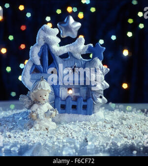 Festive New Year's, Christmas still life a fantastic toy lodge and a toy angel with a star, at night on snow. black - Stock Photo