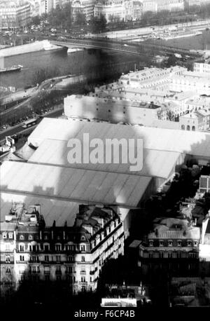 A shadow of the Eiffel Tower looms across the Seine River and the rooftops buildings in Paris, France - Stock Photo