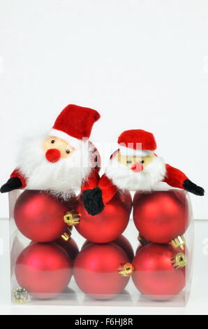 close up of a plastic box  with red Christmas tree balls and two figures of Santa Claus on white background,  vertical - Stock Photo