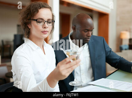 Shot of businesswoman having a glass of cocktail with a business man sitting by at bar counter. Businesspeople sitting - Stock Photo