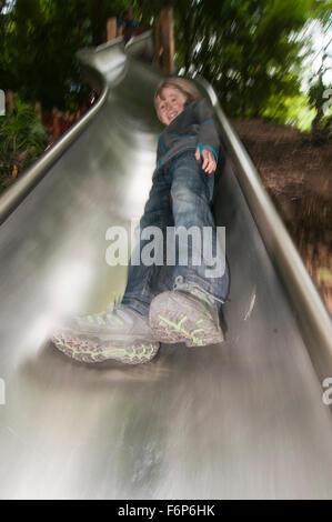 Boy coming down slide - Stock Photo