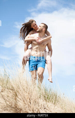 Man giving girlfriend piggyback ride on beach - Stock Photo