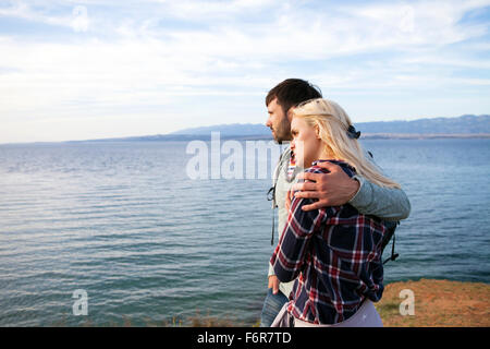 Young couple on cliff looking at sea - Stock Photo