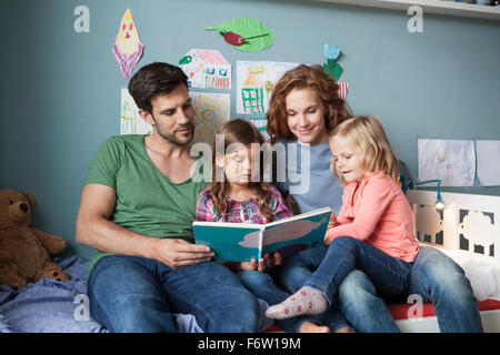 Couple and little daughters sitting together on bed in children's room reading a book - Stock Photo