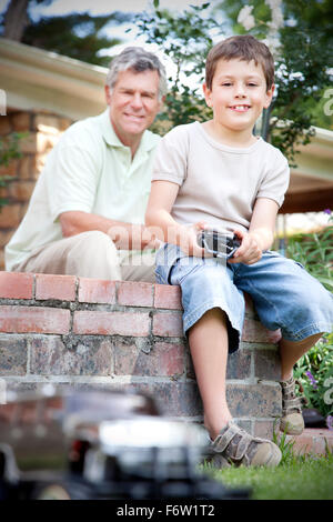 Little boy playing with toy car while his grandfather watching in the background - Stock Photo