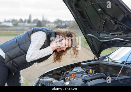 woman 's car breaks down and she is calling the emergency services - Stock Photo