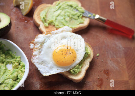 Two slices of avocado toast, one with a fried egg on top - Stock Photo