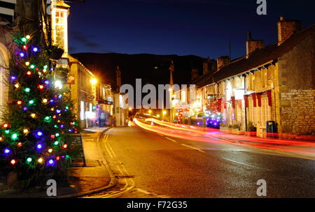 Christmas decorations light up the main street in Castleton, a village in the Hope Valley, Peak District Derbyshire - Stock Photo