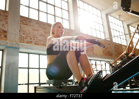 Young caucasian woman doing exercises on fitness machine in gym. Female using rowing machine at  fitness club. - Stock Photo