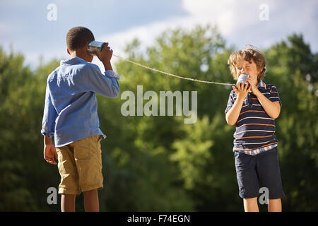 Two boys play tin can telephone in the summer - Stock Photo