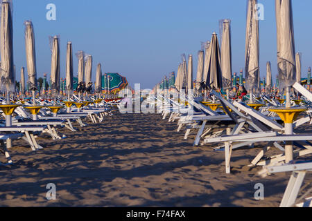 Rows of colorful umbrellas and sunbeds on sandy beach - Stock Photo