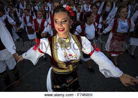 Serbian girl dressed in national costume dances traditional folklore dance 'Kolo'. Central square in Sabac, Serbia. - Stock Photo