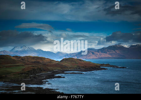 Storm clouds over the Sound of Sleat, Isle of Skye, with snow capped peaks of mainland Scotland in the background. - Stock Photo