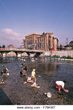 9th August 1993  Women wash laundry in the River Miljacka below the burnt-out National Art Gallery and Library in - Stock Photo