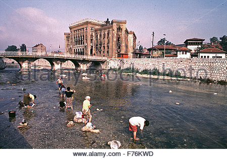 9th August 1993  Women wash clothes in the River Miljacka below the burnt out National Art Gallery and Library in - Stock Photo