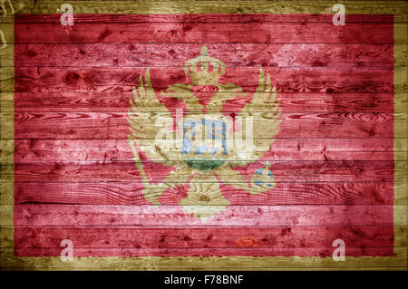 A vignetted background image of the flag of Montenegro painted onto wooden boards of a wall or floor. - Stock Photo