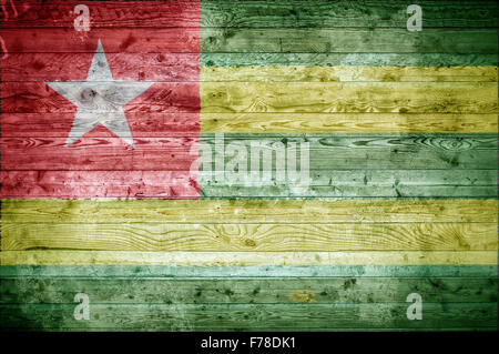 A vignetted background image of the flag of Togo onto wooden boards of a wall or floor. - Stock Photo