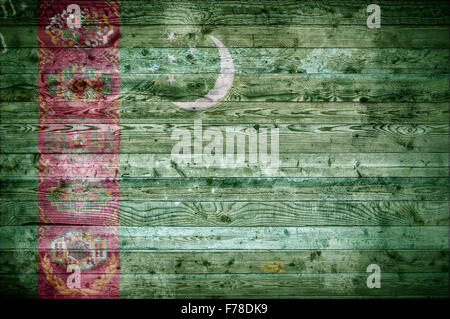 A vignetted background image of the flag of Turkmenistan onto wooden boards of a wall or floor. - Stock Photo