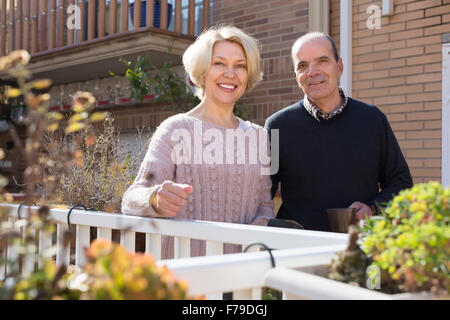 Elderly smiling woman with horticultural sundry and aged man drinking tea in patio - Stock Photo