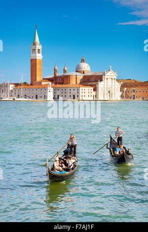 Tourists in venetian gondola on Grand Canal (Canal Grande) and San Giorgio Maggiore church in the background, Venice, - Stock Photo