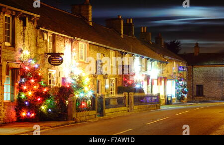 Illuminated Christmas trees line the main street in Castleton; a village in the Peak District, Derbyshire UK - Stock Photo